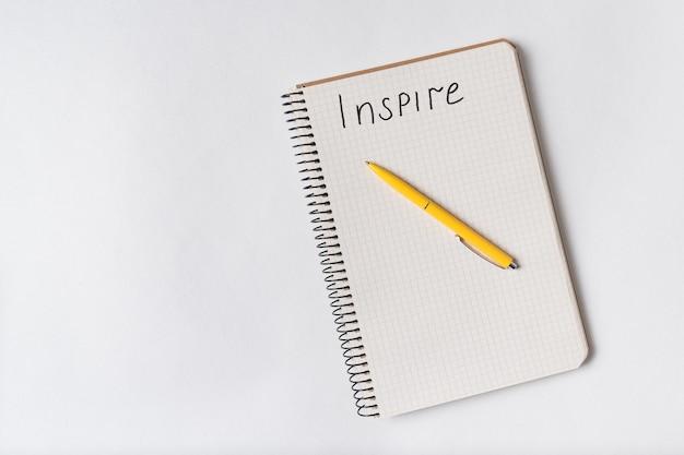 Вдохновить почерк уведомления. вид сверху блокнот и ручка на белом Premium Фотографии