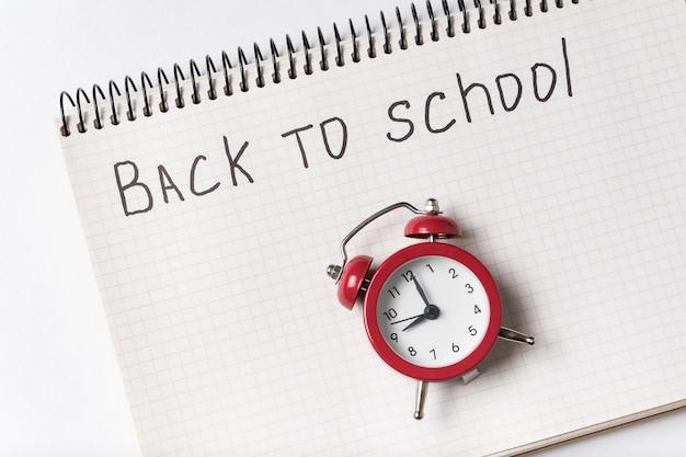 Блокнот с надписью назад в школу и старинный будильник. Premium Фотографии