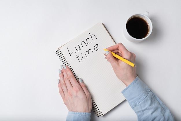 Женские руки писать слова время обеда. тетрадь и чашка кофе на белой предпосылке. Premium Фотографии