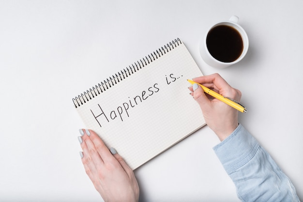 Тетрадь с текстом счастье. взгляд сверху женских рук писать в тетради, чашку кофе Premium Фотографии