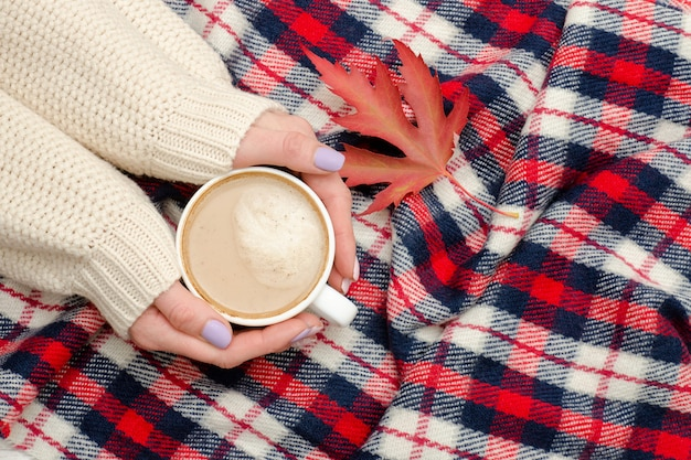 女性の手、市松格子縞、秋の葉のカプチーノ。ファッショナブルなコンセプト Premium写真