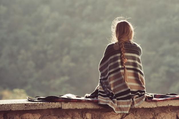 丘の上に座って自然を楽しんでいる若い女性。背面図 Premium写真