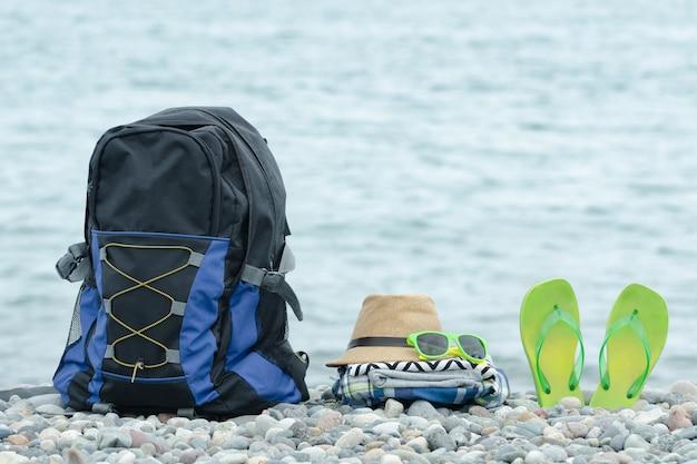 小石のビーチでバックパック、帽子、ビーチサンダル。 Premium写真