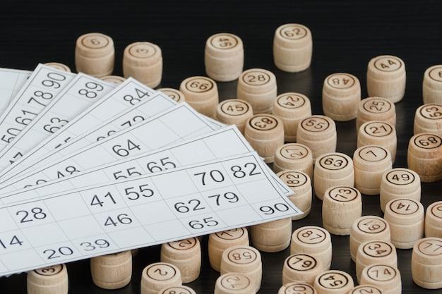 木製の樽の宝くじとカード。黒い木製のテーブル。 Premium写真