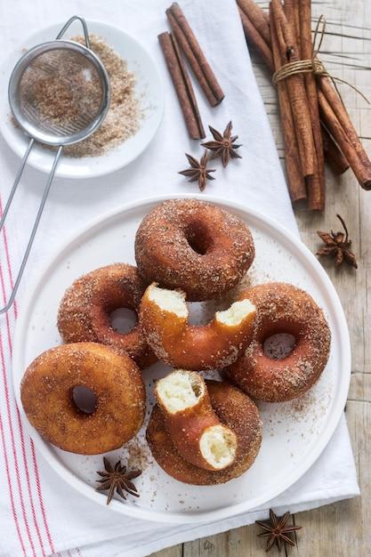 砂糖とシナモンの木製の背景と自家製ドーナツ。素朴なスタイル。 Premium写真