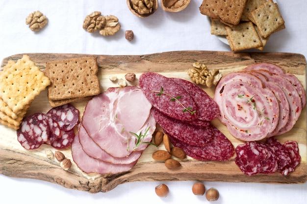 さまざまな種類のソーセージ、肉、チーズ、クラッカーの前菜。 Premium写真