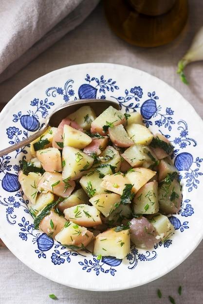 Традиционный салат из холодного картофеля с луком и зеленью на фоне льняной скатерти. деревенский стиль Premium Фотографии