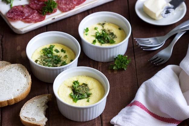Завтрак омлет, колбаса, хлеб с маслом на темном фоне. Premium Фотографии