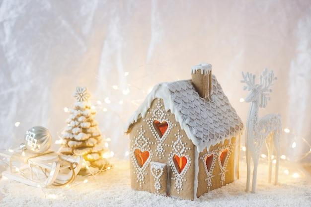 ジンジャーブレッドの家、クリスマスツリー、明るい背景に鹿の姿。ボケ効果。 Premium写真
