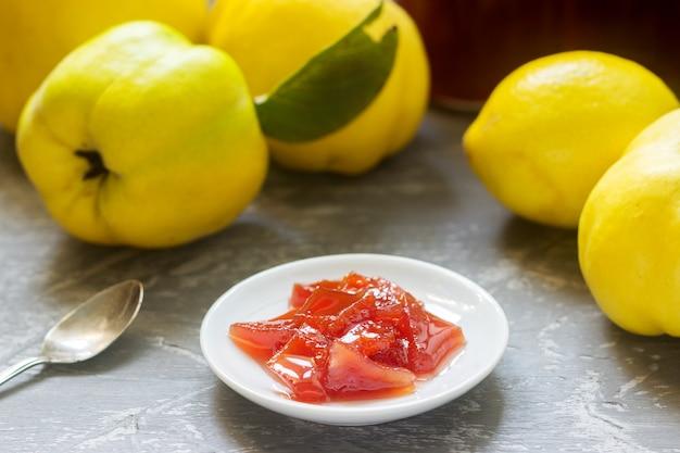 Айва варенье на белом блюдце, айва фрукты и банки с вареньем на сером фоне. Premium Фотографии
