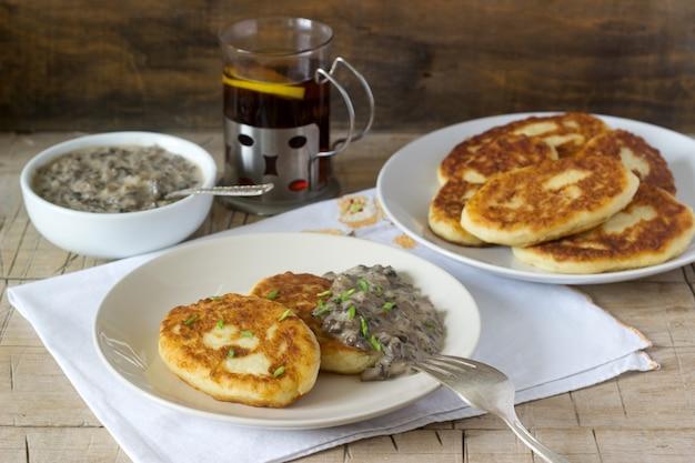 ポテトカツレツまたはパンケーキとマッシュルームソースとねぎ。素朴なスタイル。 Premium写真