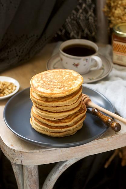 バナナ、ナッツ、蜂蜜入りのパンケーキにお茶を添えて。素朴なスタイル。 Premium写真