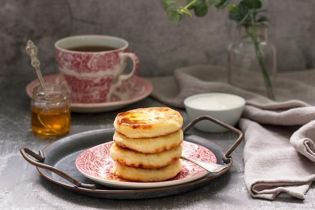カッテージチーズのパンケーキ、自家製蜂蜜とサワークリームのシロニキ。 Premium写真