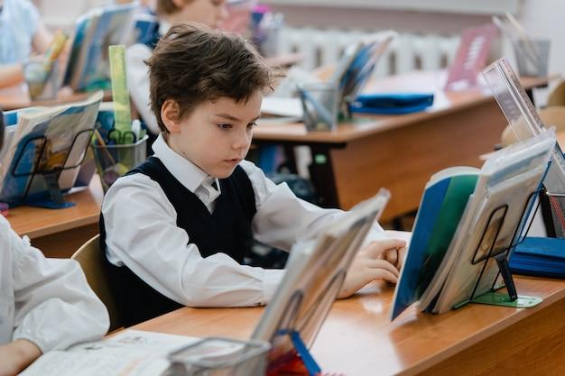 若い男子生徒は教室で本を見て集中しました Premium写真