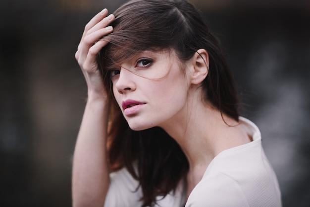 秋の公園で黒髪と美しい首を持つ魅力的な若い女性。 Premium写真