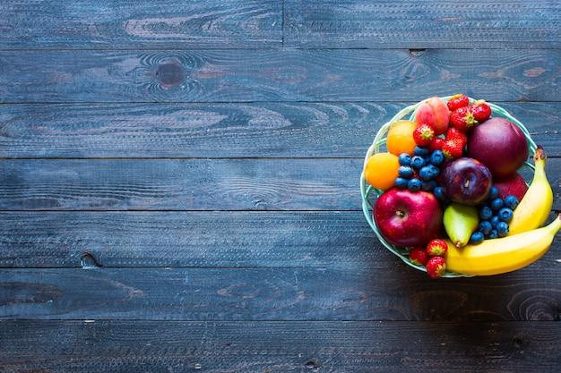 Чаша из свежих фруктов с бананом, яблоками, клубникой, абрикосами, черникой, сливами, цельными зернами, вилками, вид сверху Premium Фотографии