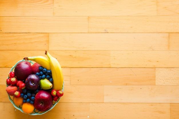 バナナアップルイチゴと新鮮なフルーツのボウルアプリコットブルーベリープラム全粒粉フォークトップビュー Premium写真