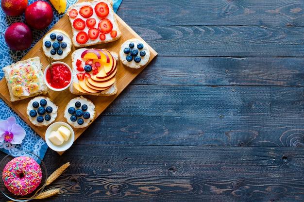異なる木製の背景に異なるフィリングチーズバナナイチゴ釣りバターブルーベリーとおいしい健康的な朝食フルーツサンドイッチ。 Premium写真