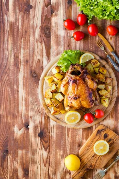 Домашняя запеченная курица с лимоном и картофелем на деревянном фоне Premium Фотографии