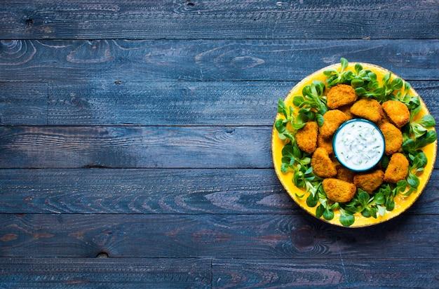 Куриные наггетсы с йогуртовым соусом на деревянном фоне Premium Фотографии