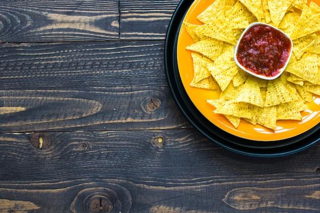Мексиканские чипсы начос на деревянном фоне Premium Фотографии