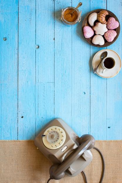 古いビンテージ電話、ビスコッティ、コーヒー、木製の背景にドーナツ Premium写真