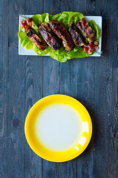 Жареные свиные ребрышки барбекю с овощами на деревянном фоне; Premium Фотографии