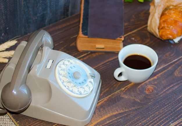 Старый винтажный телефон, кофе, книга, на деревянной предпосылке, Premium Фотографии