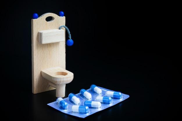 木のおもちゃのトイレとカプセルブラック Premium写真