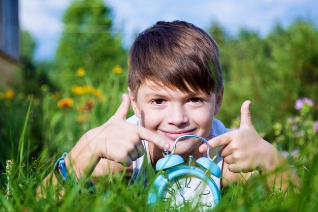 夏の庭で目覚まし時計を持つ少年を産む Premium写真