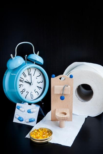 木のおもちゃのトイレ、錠剤、黒の目覚まし時計 Premium写真