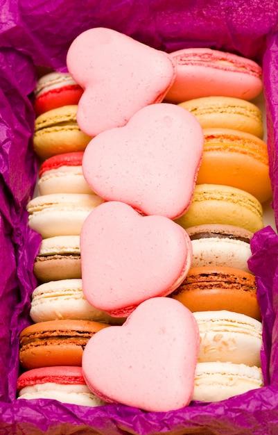 紫色の背景にハートとフランスのカラフルなマカロン Premium写真