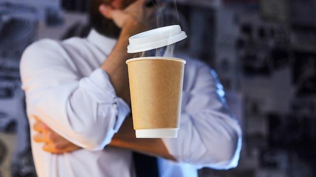 Бариста и парящий бумажный стаканчик с горячим кофе Premium Фотографии
