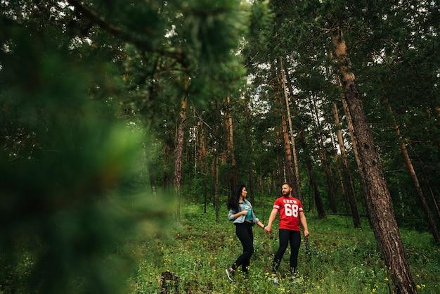 Влюбленная пара гуляет по хвойному лесу. парень и девушка гуляют в лесу. мужчина и женщина, держась за руки. пара в зеленом лесу. влюбленная пара держатся за руки в лесу. подписывайтесь на меня Premium Фотографии