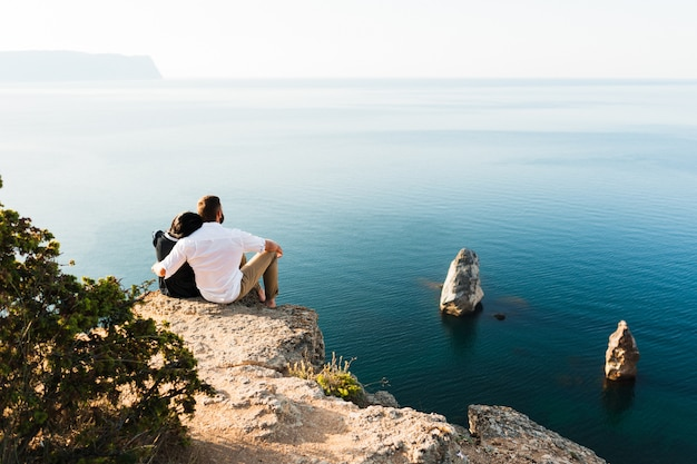 海沿いの崖の端に座っている男女。ハネムーン。新婚旅行。海の男と女。男と女の旅行。カップルが抱擁します。カップルがキスします。新婚カップル。恋人 Premium写真