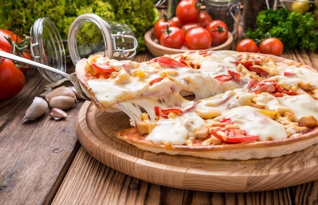 チーズを溶かした木製のトレイにおいしいホットピザ Premium写真