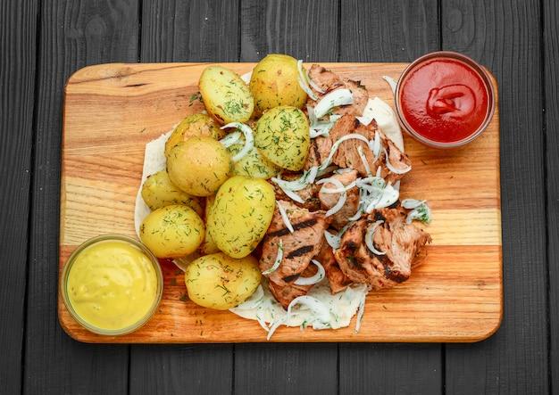 Мясо на гриле с отварным картофелем и овощами Premium Фотографии