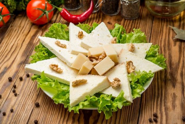 Домашний мягкий сыр сулугуни с помидорами, паприкой, луком и свежим базиликом на деревянной доске Premium Фотографии