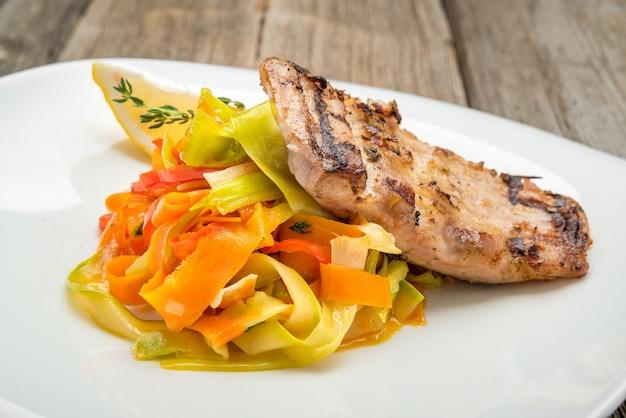 Зажаренный салат карпа и свежего овоща рыб на деревянной предпосылке. Premium Фотографии