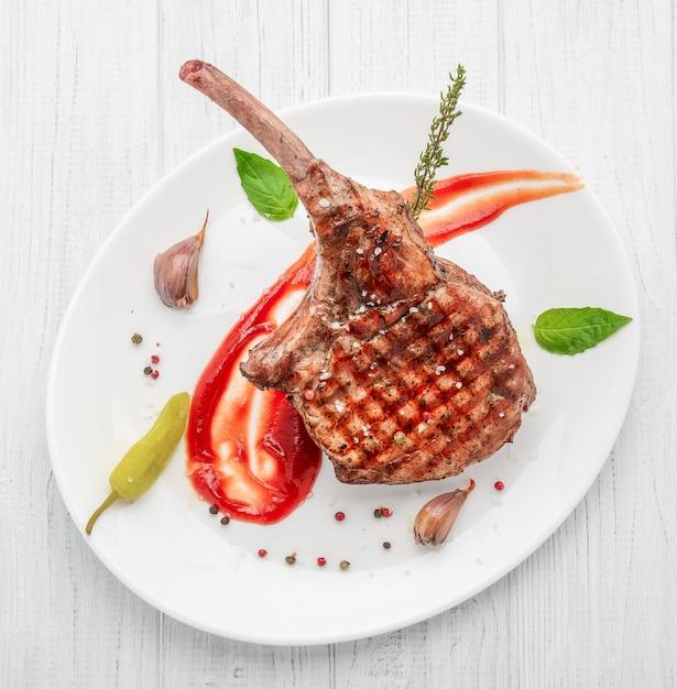 骨のステーキ。白い木製のテーブルにトマホークステーキ。上面図。 Premium写真