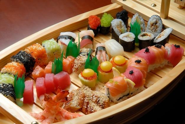 Корабль с суши и роллами на темной поверхности Premium Фотографии