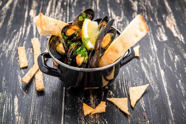 Мидии в металлическом кулинарном блюде и французский багет с зеленью Premium Фотографии