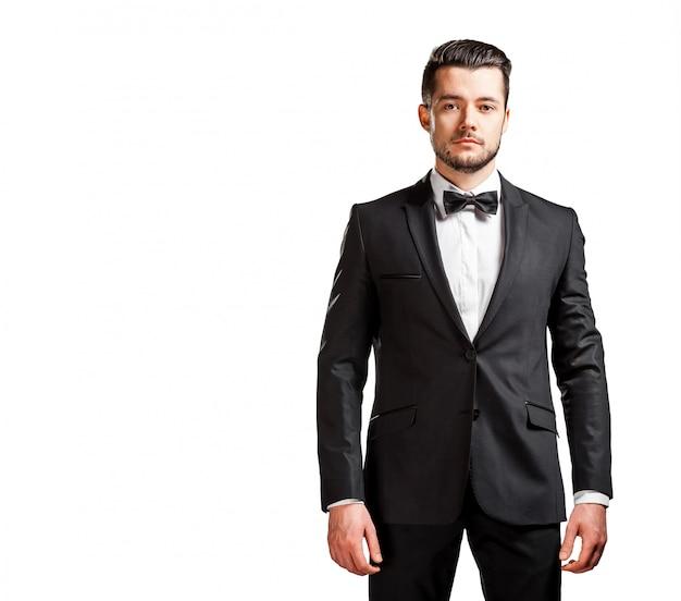 ボウタイと黒のスーツで自信を持ってハンサムな男の肖像 Premium写真