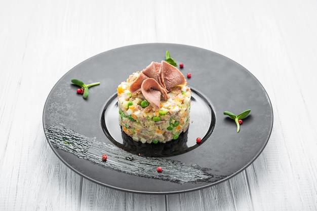 健康的な自家製ロシアの伝統的なサラダオリビエプレートで食べる準備ができて、クローズアップ Premium写真
