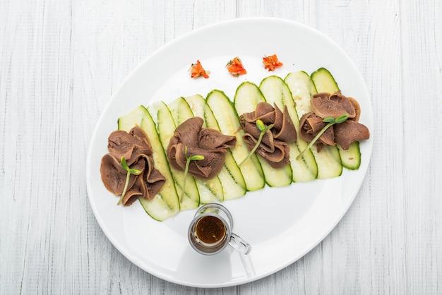 ペストとサラダと暗い木製のテーブルにゆでた牛タン Premium写真