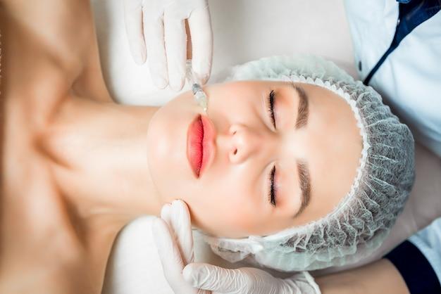 美容師は、美容院の美しい若い女性の顔の皮膚のしわを引き締めて滑らかにするための若返りフェイシャル注射手順を行います Premium写真