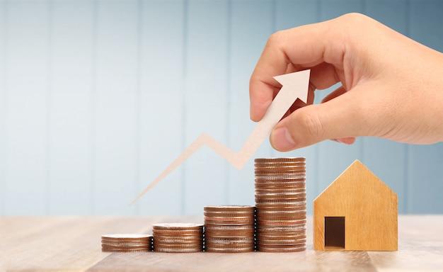 木のおもちゃの家の住宅ローンのプロパティホームコンセプト家族、コインを手に購入 Premium写真