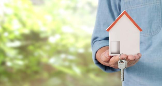 不動産業者が家の鍵を手に引き渡す Premium写真