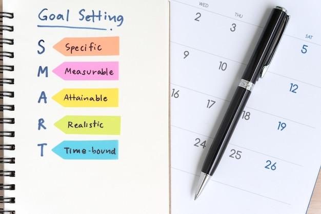 カレンダー付きのノートブックで頭字語を設定するスマートな目標 無料写真
