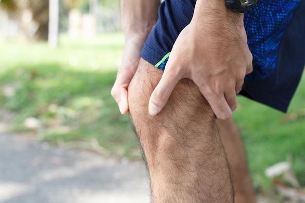 実行後の膝の怪我を実行しているスポーツの痛みで苦しんでいるスポーツ男のクローズアップ。トレーニングの概念からの怪我。 Premium写真